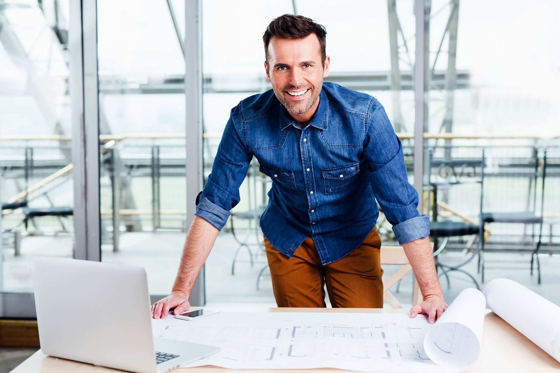 An Architect Standing over Drawings at the Office